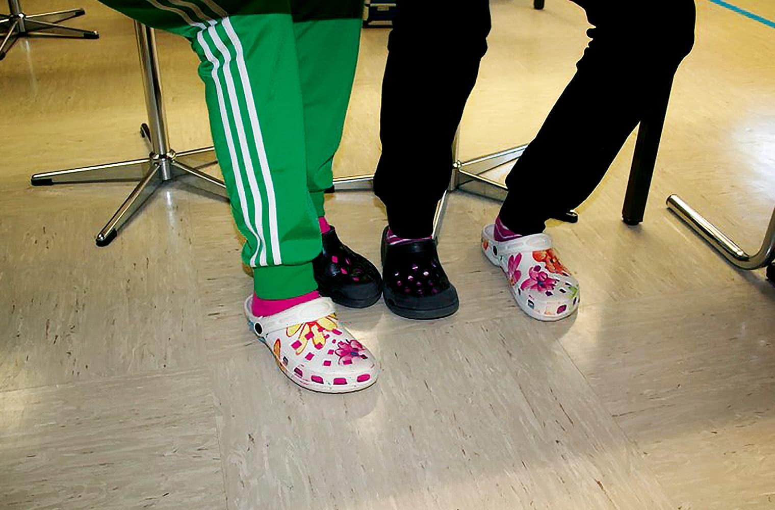 2 Schüler haben das Schuhwerk getauscht, sodass jeder zwei verschiedene Sandalen anhat.