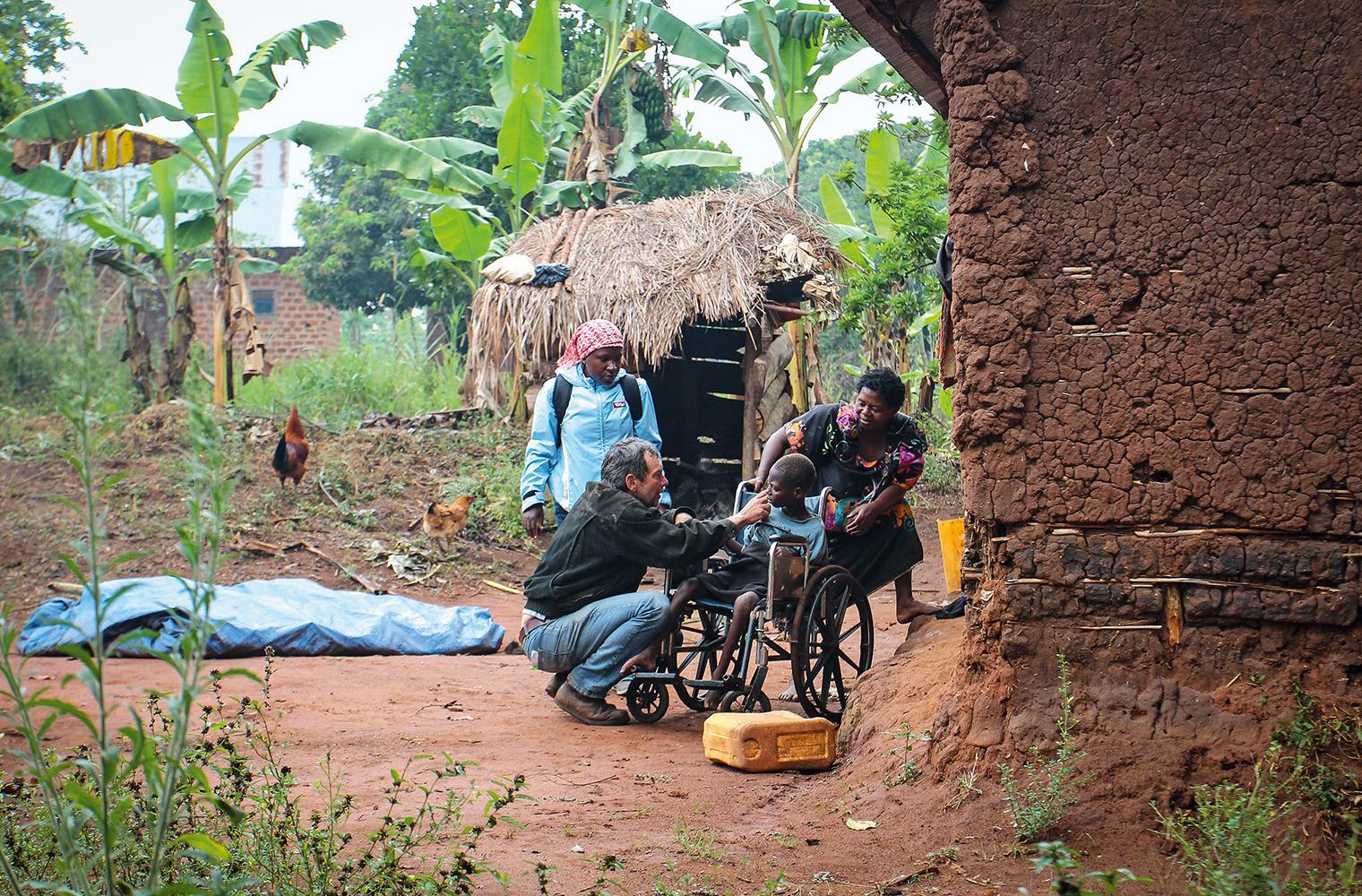 Angelina sitzt im Rollstuhl. Ein Mann stupst sie an der Nase. Ihre Mutter und eine Sozialarbeiterin verfolgen die Szene.