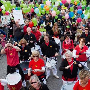 Auf einer Straße sind viele Menschen mit Trommeln, Luftballons und Transparenten unterwegs.
