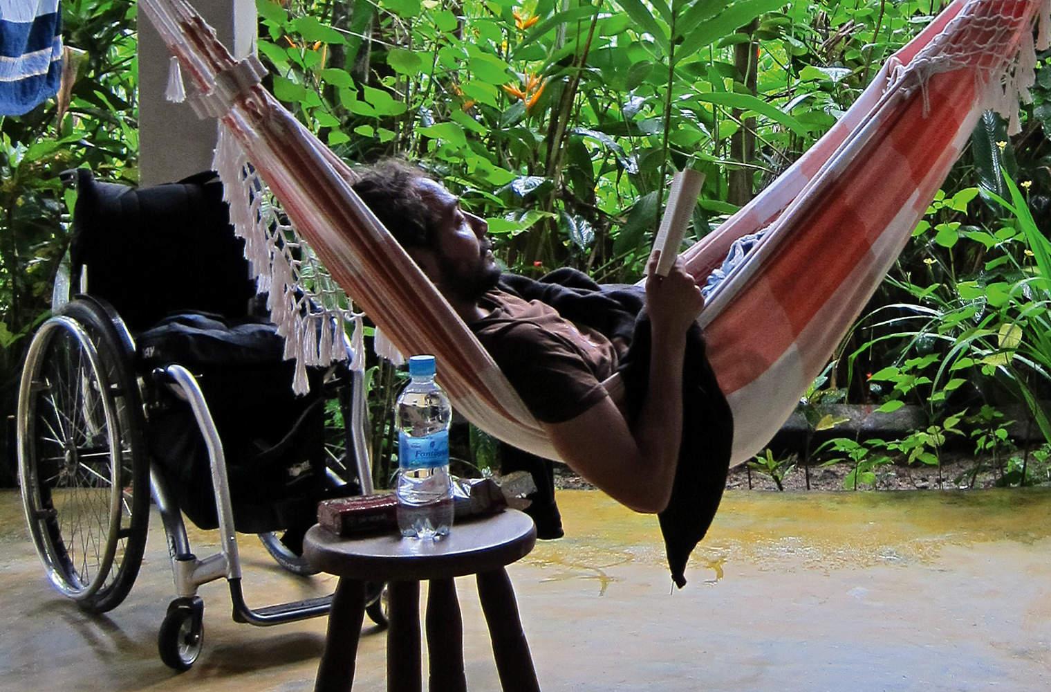 Autor Reinfried Blaha genießt auf einer Terrasse umgeben von grünen Pflanzen das Leben. Er liegt bequem in einer Hängematte und liest ein Buch. Dan...