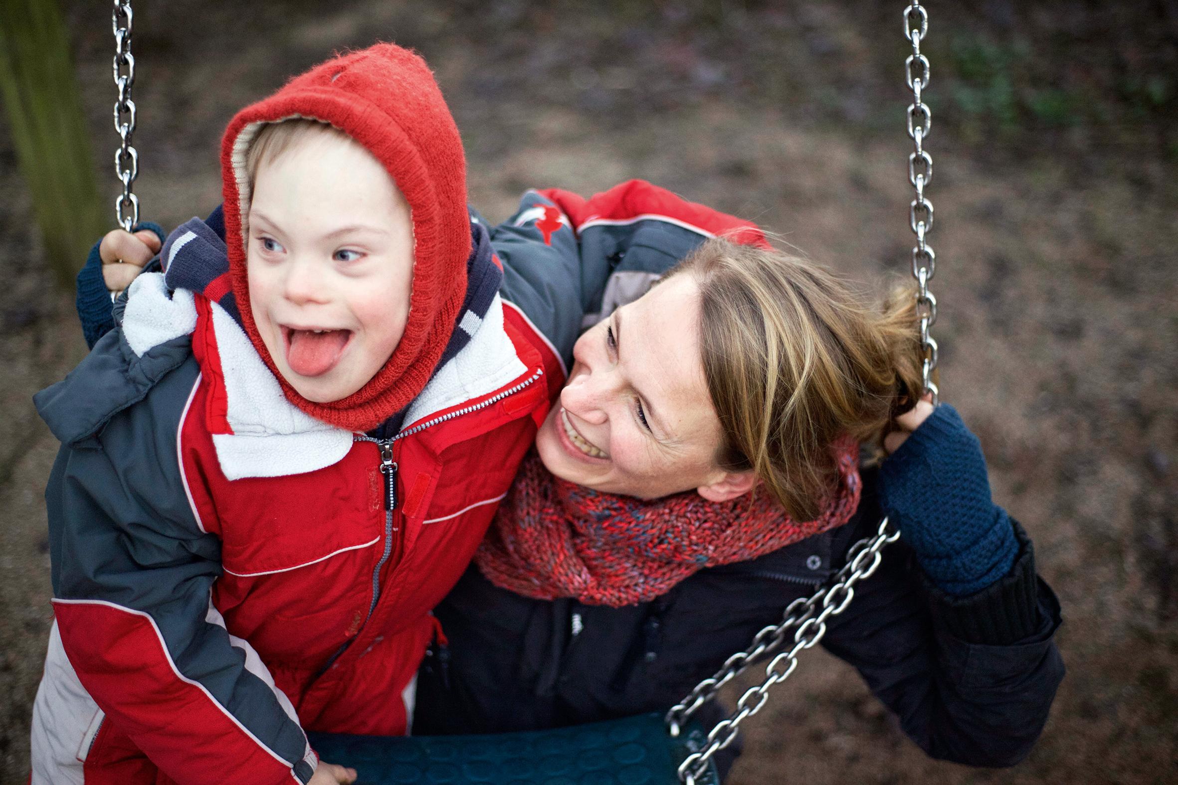 Birte Müller beugt sich zu ihrem Sohn Willi auf einer Kinderschaukel. Beide lachen herzlich.