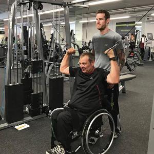 Der ehemalige Rollstuhlbasketballer Dirk Schmitz übt an einem Fitnessgerät. Sein Trainer Thomas Gessler steht dahinter.