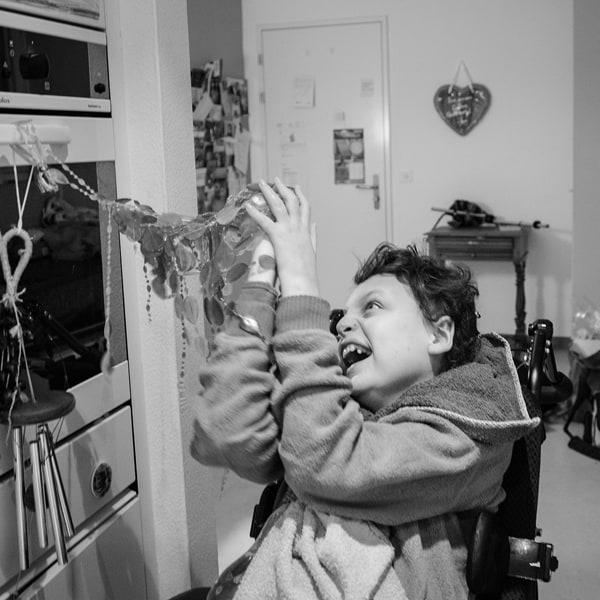 Der im Rollstuhl sitzende Yorick zieht mit freudigem Gesicht an Raschelketten, die in seiner Augenhöhe am Griff eines Küchenherdes festgemacht sind...