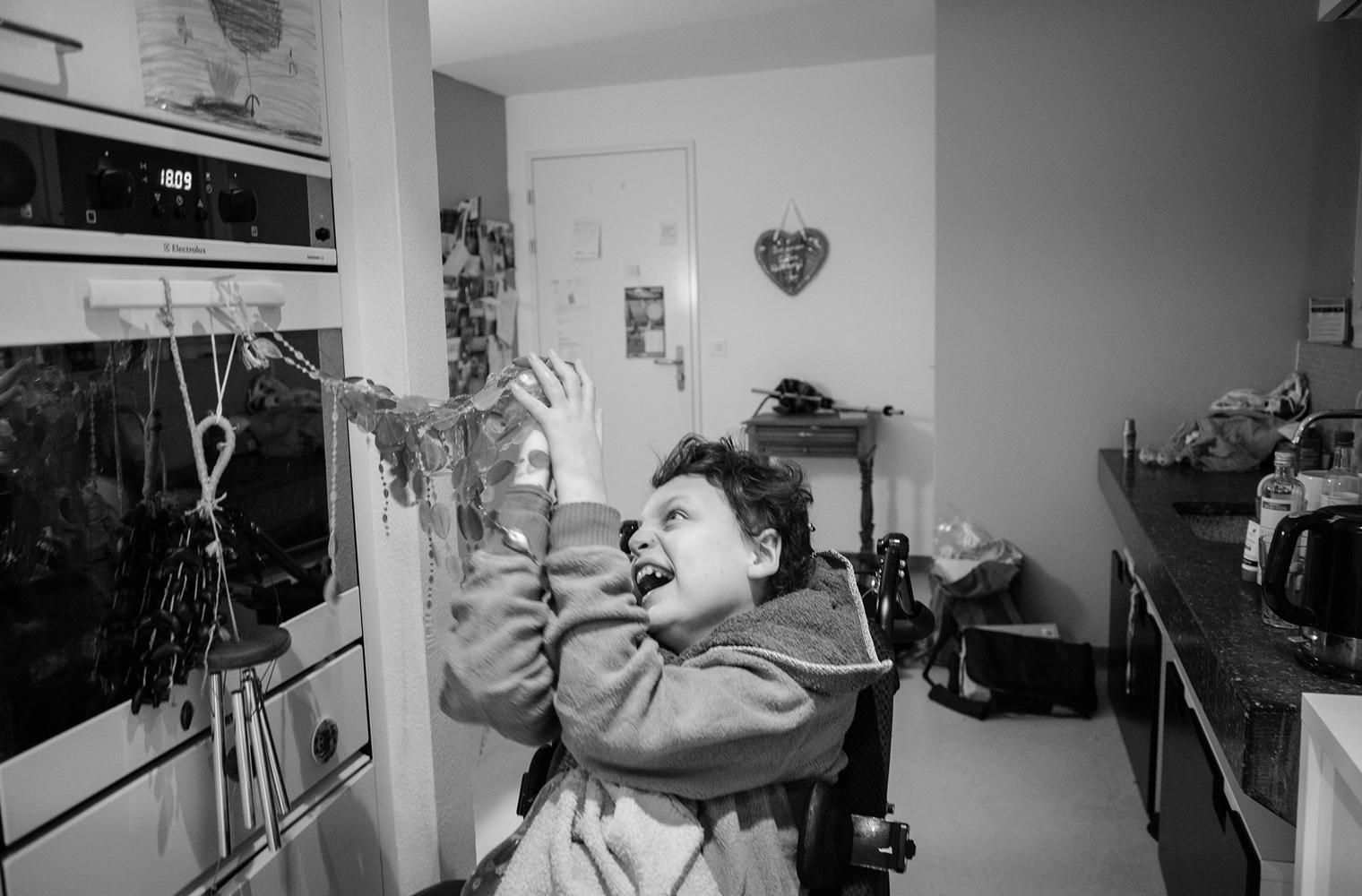 Der im Rollstuhl sitzende Yorick zieht mit freudigem Gesicht an Raschelketten, die in seiner Augenhöhe am Griff eines Küchenherdes festgemacht sind.