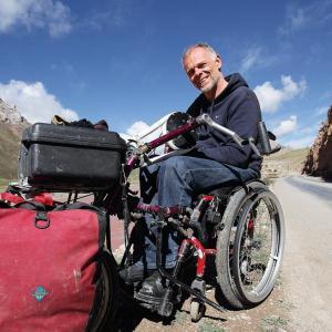 Der Reisejournalist Andreas Pröve sitzt in seinem Rollstuhl auf einer staubigen Landstraße im Hochland von Tibet - Foto: Andreas Pröve