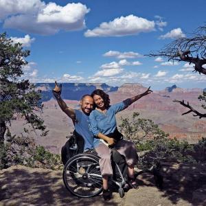 Der rollstuhlfahrende Autor hat seine Freundin am Schoß. Beide lachen freudig und zeigen in die Landschaft. Hinter den beiden sieht man die Felsfor...
