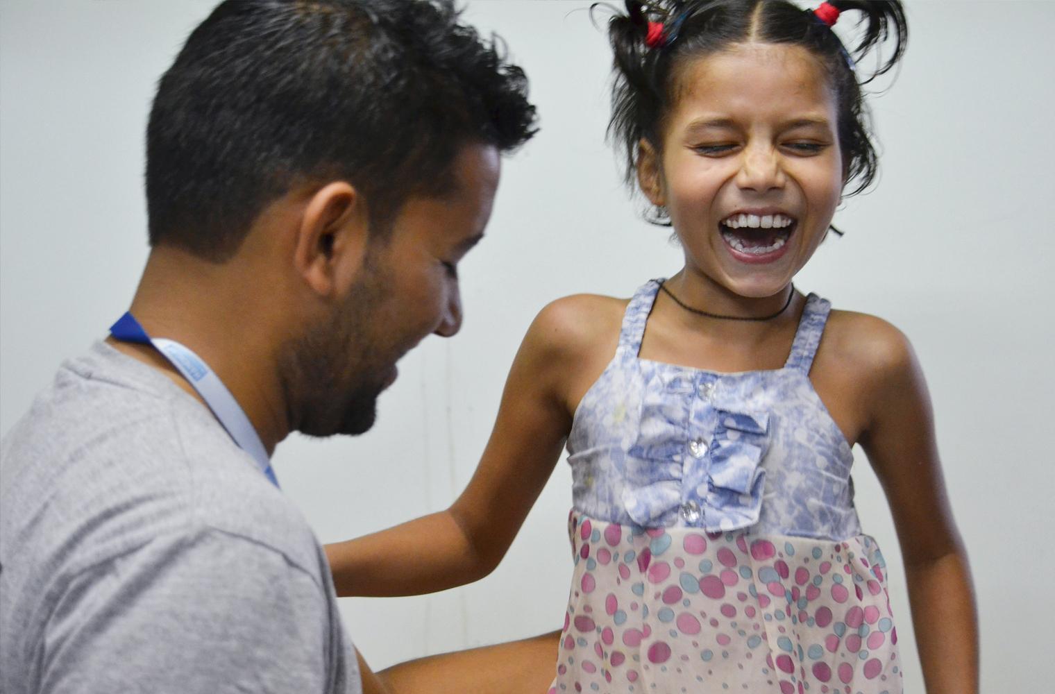 Die beinamputierte siebenjährige Nirmala lacht fröhlich im Gespräch mit einem jungen Arzt in Nepal.