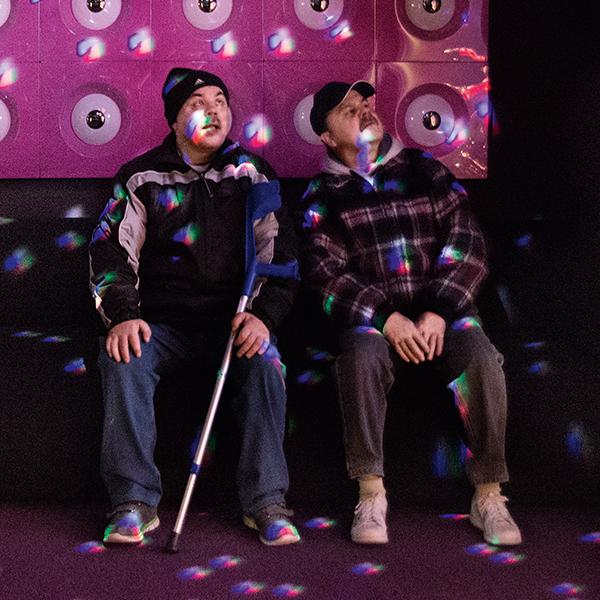 Die taubblinden Zwillingsbrüder Jörg und Rolf Fischer sitzen in einem in farbiges Licht getauchten Raum und spüren die Lichtreflexe.
