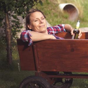 Egoistinnen - Birte Müller: Die Autorin liegt ganz entspannt mit einer Bierflasche in der Hand in einem Ziehwagerl.