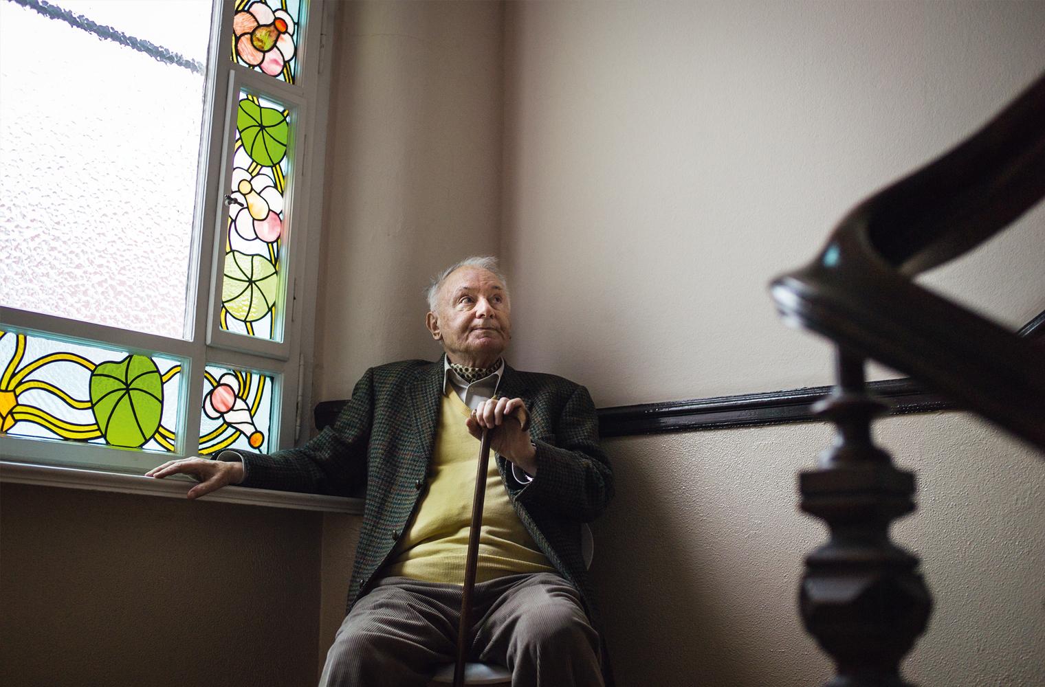 Ein älterer Herr sitzt auf einem Sessel im Eck eines Stiegenaufganges.
