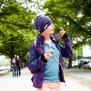 Ein Mädchen mit Haube, Jacke und über dem T-Shirt sichtbarem Ernährungsschlauch spaziert durch eine Straßenallee entlang eines Flusses. Im Hintergr...