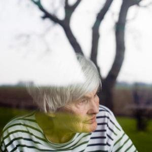 Eine ältere Dame steht am geschlossenen Fenster und schaut in den Garten.