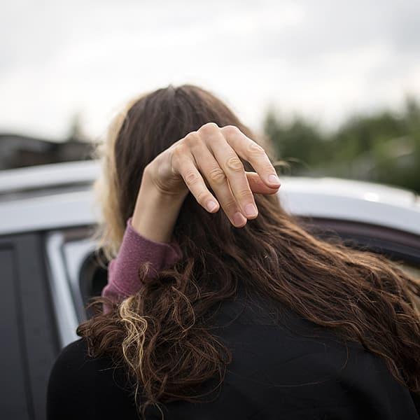 Eine Frau – sie hat MS – wird aus dem Auto gehoben. Ihre rechte grazile Hand hält sich an der Schulter einer anderen Frau fest.