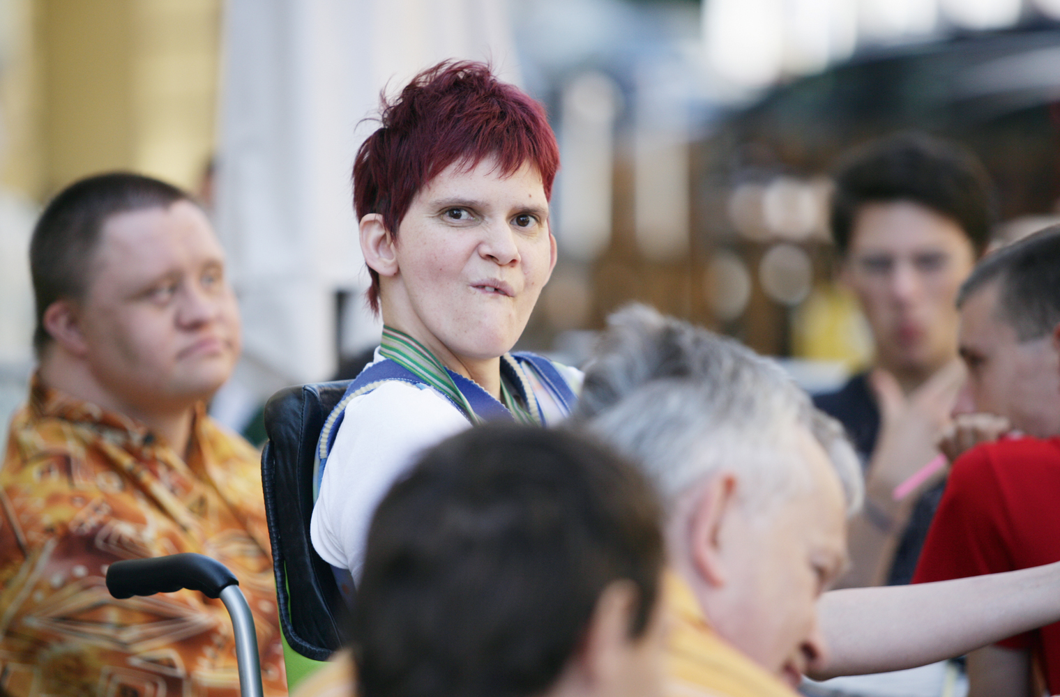 Eine junge Frau mit Behinderung schaut erstaunt in die Runde.