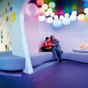 Eine Mutter umarmt ihr Kind. Beide sitzen in einem farbigen und lichtdurchtränkten Raum und sind sichtlich beeindruckt.
