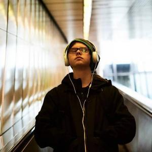 Emil, 13 Jahre alt, ist ein cooler Junge mit Trisomie 21: Er trägt Brillen, eine Haube hat die Hände in seiner schwarzen Jacke.