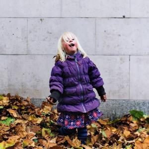 Emmy ist ein fünf Jahre altes, aufgewecktes Mädchen mit Trisomie 21. Mit ihren langen, blonden Haaren steht sie mitten im Laub und hält ein Blatt.