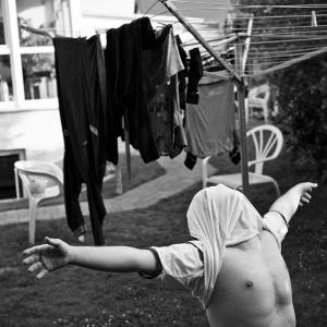 Fotos aus dem Leben des 21 jährigen Sven-Erik mit Trisomie 21. Hier hat er sich sein T-Shirt über den Kopf gezogen und steht mit ausgebreiteten Ar...