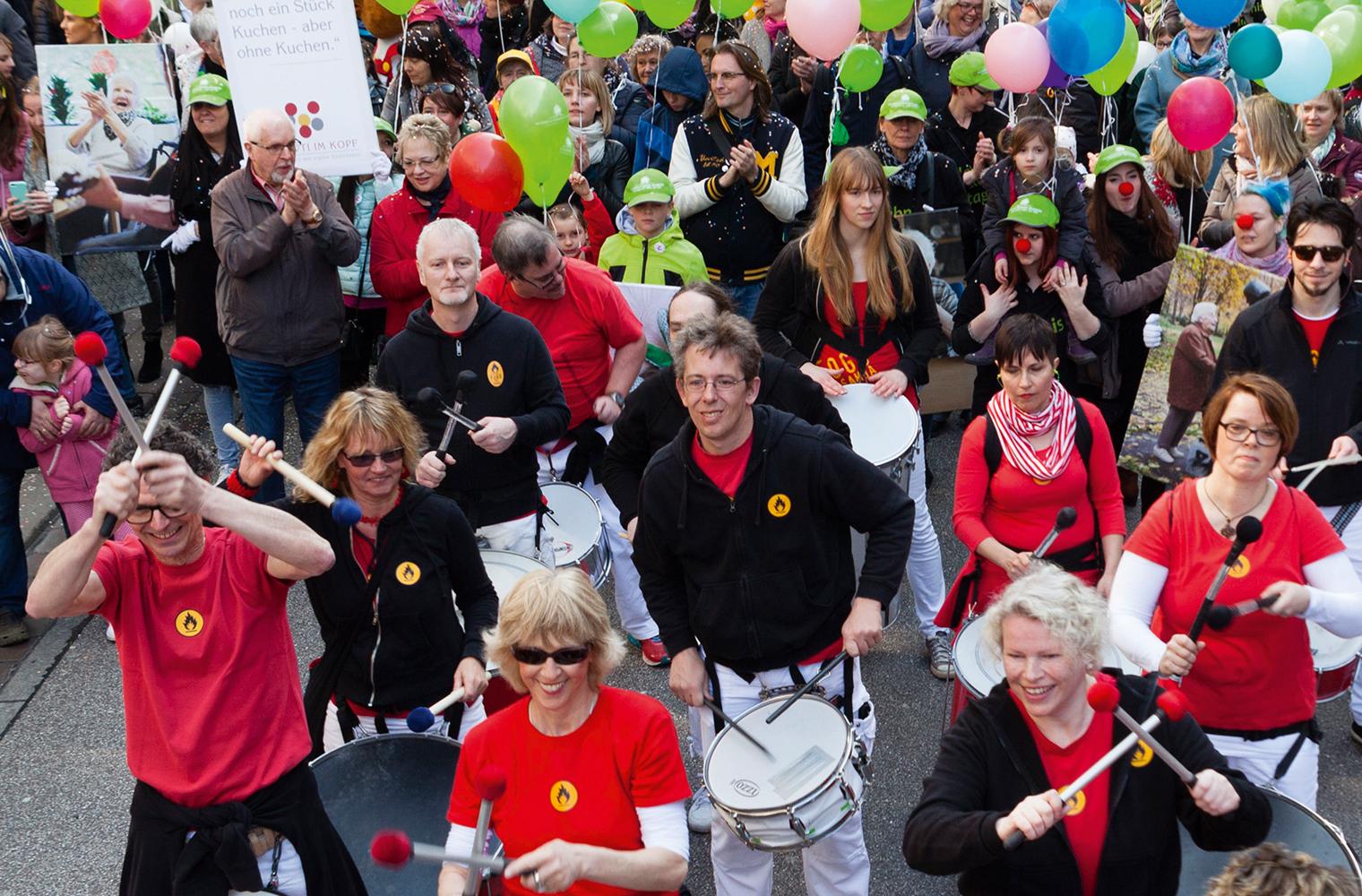 Gerhard Einsiedler: Auf einer Straße sind viele Menschen mit Trommeln, Luftballons und Transparenten unterwegs.