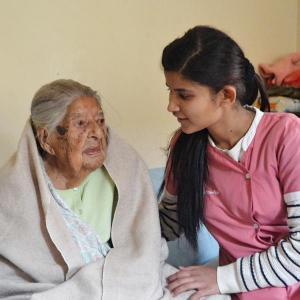 Haus für Menschen mit Demenz in Nepal - Lea Frei: Eine junge nepalesische Pflegerin sitzt neben einer älteren Frau, die in eine Decke eingehüllt is...