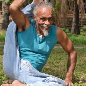 Layenda Franco sitzt am Boden und hält in einer Yogastellung das rechte Bein hochgezogen hinter der rechten Schulter. – Foto: Lea Frei