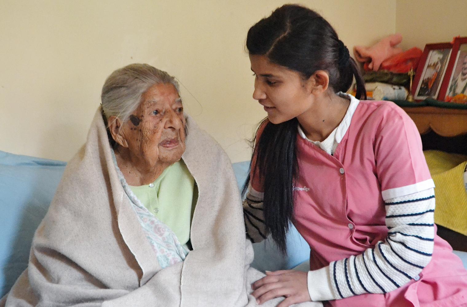 Lea Frei: Eine junge nepalesische Pflegerin sitzt neben einer älteren Frau, die in eine Decke eingehüllt ist, auf einer Couch und unterhält sich mi...