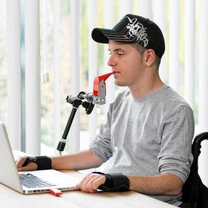 LIFEtool (Ein junger Mann sitzt am Tisch vor seinem Laptop und bedient das Gerät mit einer Mundsteuerung)