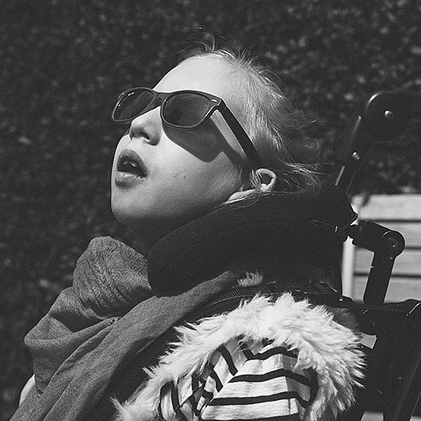 Lotta mit Sonnenbrille sitzt auf einer Parkbank und schaut staunend, mit leicht geöffnetem Mund in den Himmel.