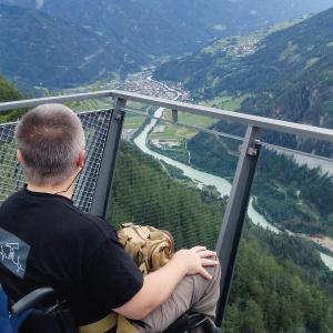 Manfred W.K. Fischer: Der Autor sitzt in seinem Rollstuhl auf einer Aussichtsrampe und genießt den weiten Blick in ein unter ihm liegendes Flusstal...