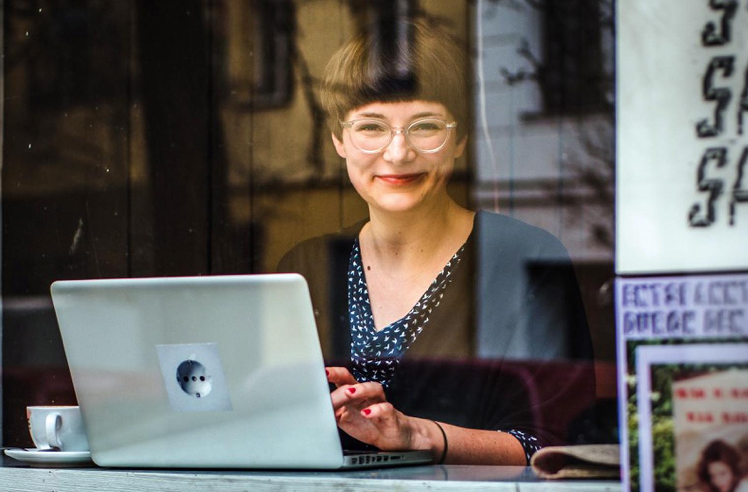 Mareice Kaiser sitzt hinter der Glasscheibe eines Cafés mit aufgeklapptem Laptop und einer Kaffeetasse daneben an einem Tisch, tippt und schaut gle...