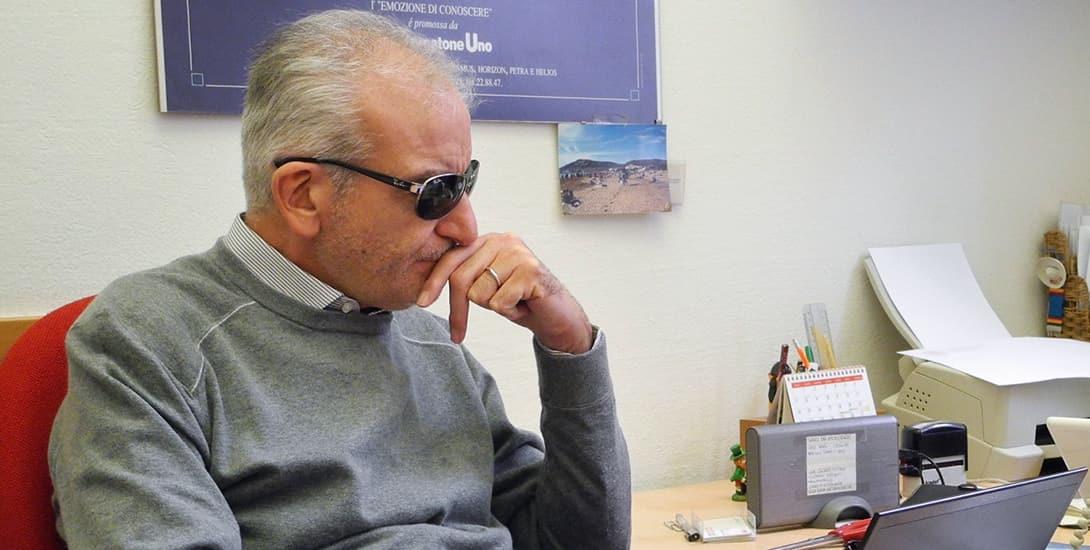 Prof. Nicola Cuomo mit dunkler Brille sitzt vor dem Laptop und überlegt angestrengt. Foto Stefan Meyer
