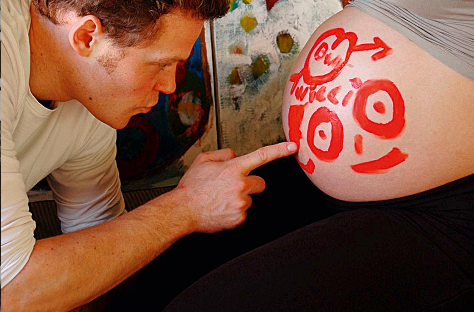 Sanft mit dem Zeigefinger bemalt der Partner von Birte Müller deren hochschwangeren nackten Bauch mit einem lachenden Gesicht, dem Symbol für männl...