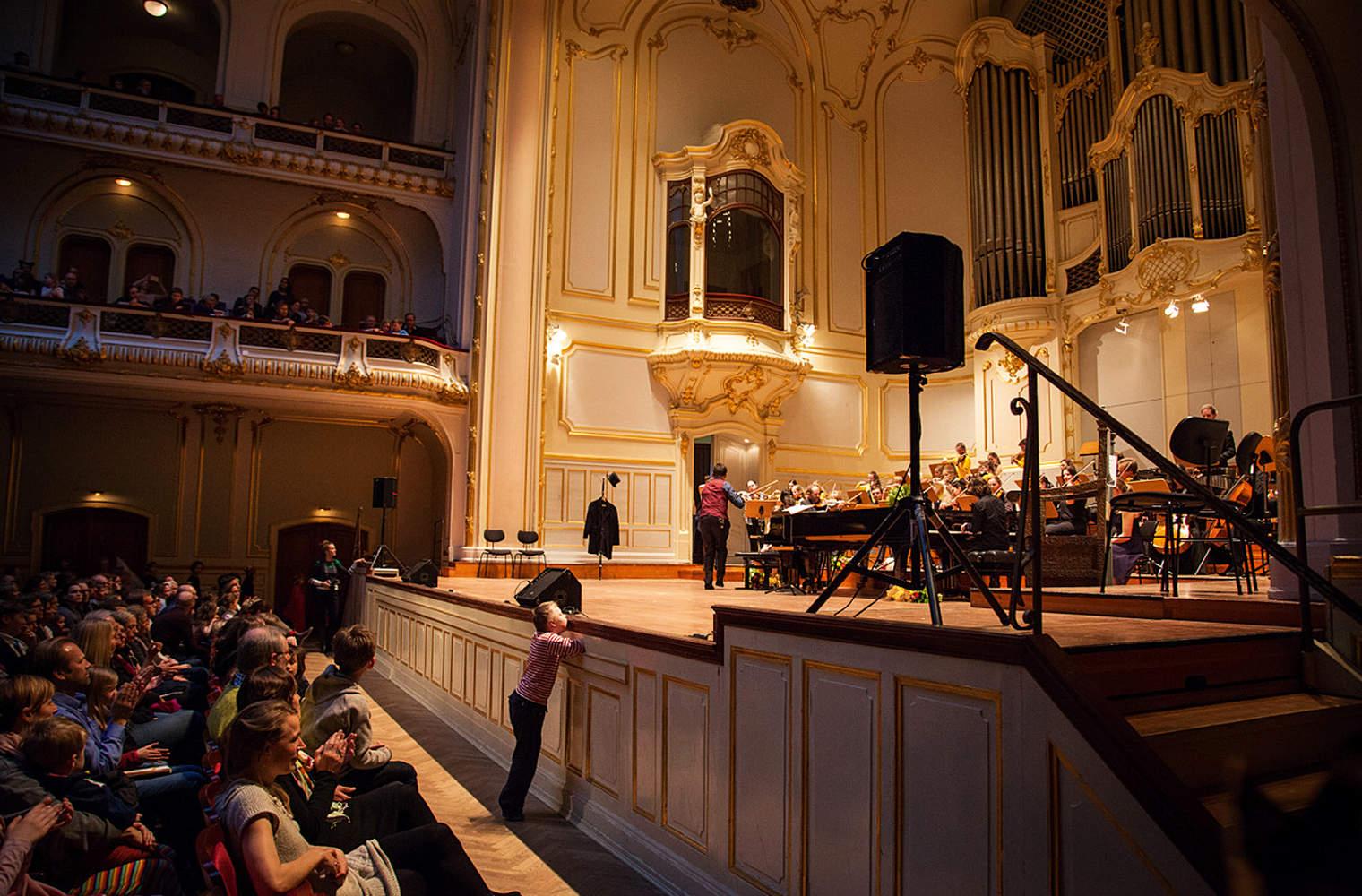 Willi, der Sohn der Autorin, steht in einem Konzertsaal ganz vorne an der Bühne, um den Musikerinnen und Musikern ganz nahe zu sein.