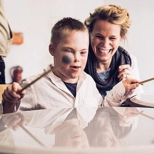 Willi sitzt vor einer großen Trommel und bearbeitet diese lustvoll mit zwei Schlägeln, seine Mutter lacht im Hintergrund.