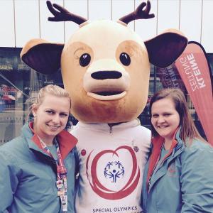 Zwei Studentinnen haben das überlebensgroße Maskottchen der Special-Olympics-Weltwinterspiele 2017 in ihre Mitte genommen und lächeln in die Kamera...