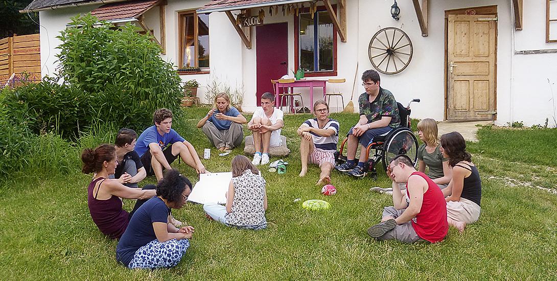 Zwölf Menschen – einer im Rollstuhl, einer mit Down-Syndrom – sitzen im Halbkreis in der Wiese und genießen ihr Zusammensein.