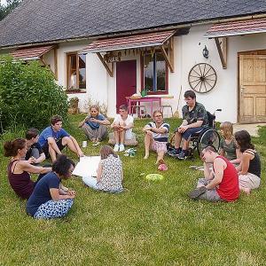 Zwölf Menschen – einer im Rollstuhl, einer mit Trisomie 21 – sitzen im Halbkreis in der Wiese und genießen ihr Zusammensein.